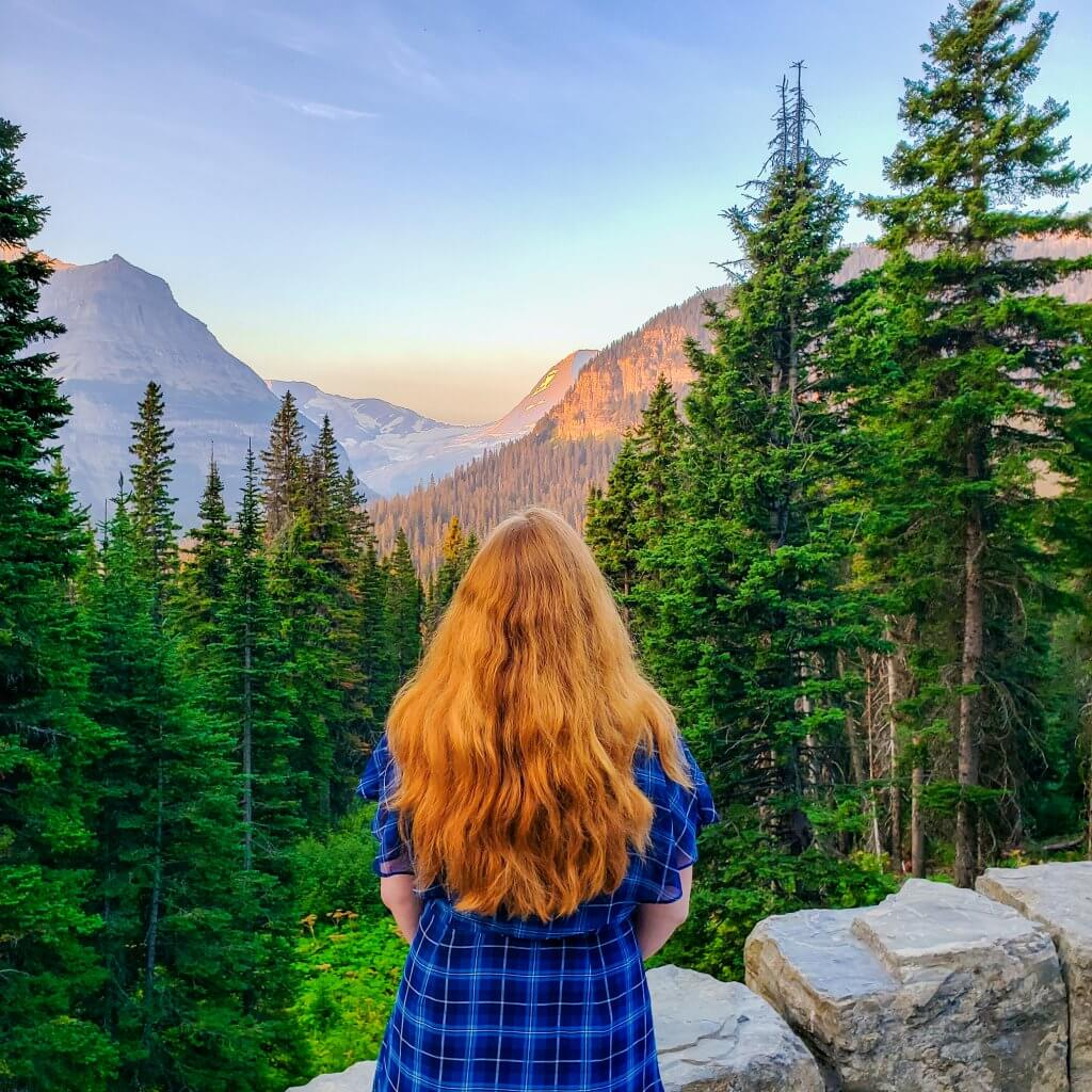 sunrise in the mountains at Jackson Glacier as Girl with blonde hair and blue plaid dress looks over a pine forest and watches the sunrise over the mountains in the distance in Glacier National Park