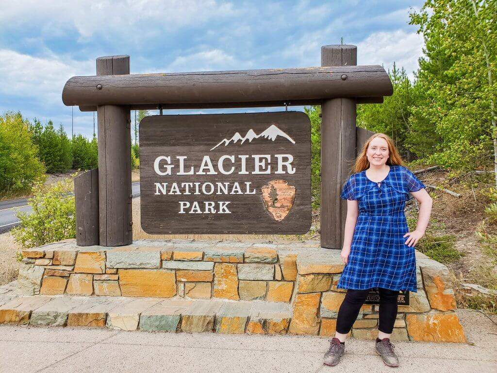 Glacier National Park Sign and Girl Standing by it in Blue Plaid Dress