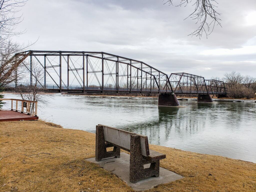 a bench on the bank of the Missouri River overlooks Fort Benton bridge